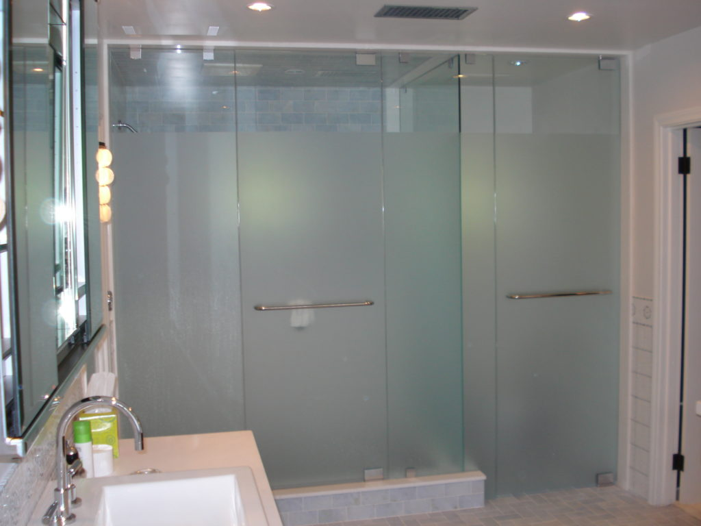 Remodeled master bath with white glass panels